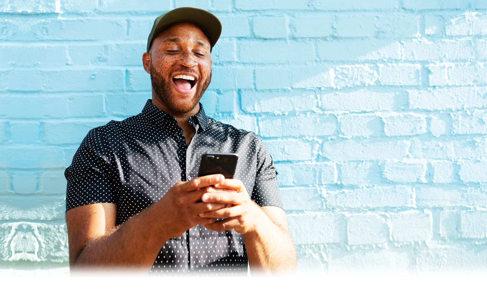 Man looking at phone and smiling against a blue brick wall