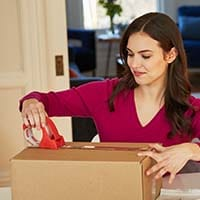 Woman closing up a box with clear tape
