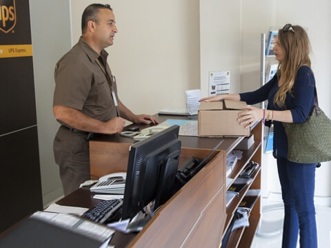 A woman wants to ship a personal shipment parcel at a UPS counter.
