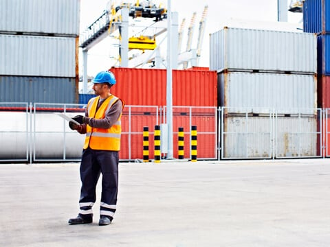 Man with high vis jacket and hard hat tracking container shipments