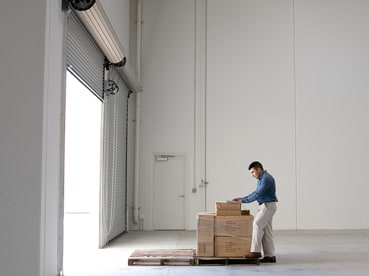 Man with parcels in warehouse