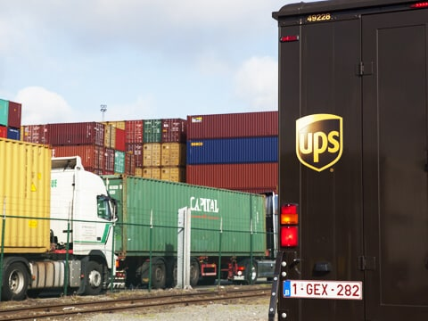 UPS car in port against the background of containers (UPS Import Control)