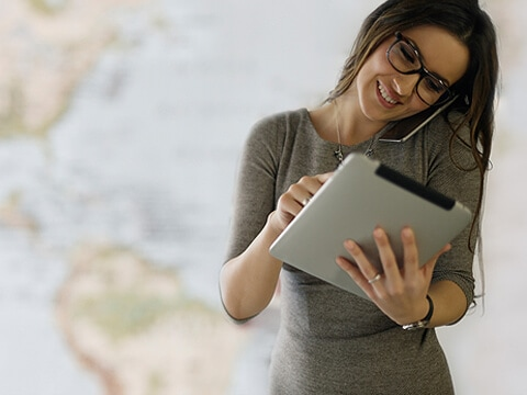 woman works using a tablet while talking on the phone against the background of the map