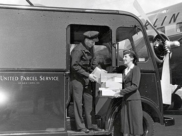 UPS employees and a delivery vehicle at an airport.