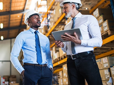 Two men in hard hats in an industrial warehouse