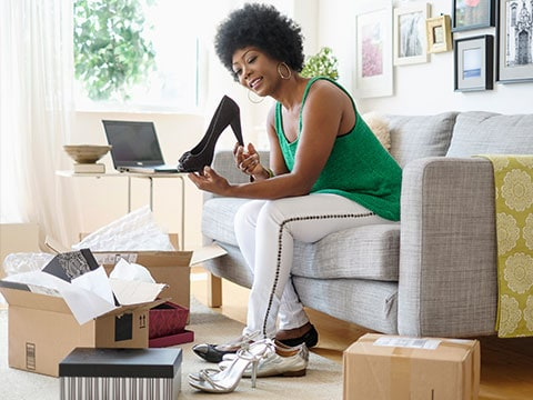 Black woman at home examining a black high heeled shoe and smiling