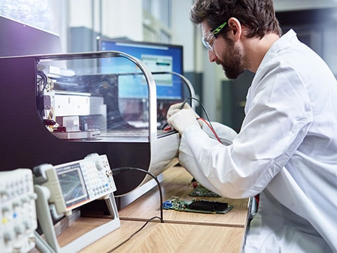 Man wearing protective goggles working in a laboratory with a 3D printer