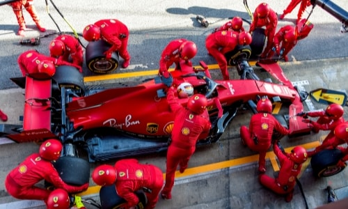 Pit crew members work on the red, UPS-branded Ferarri F1 race car.