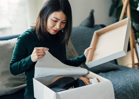 Woman opening box with a pair of shoes she ordered.