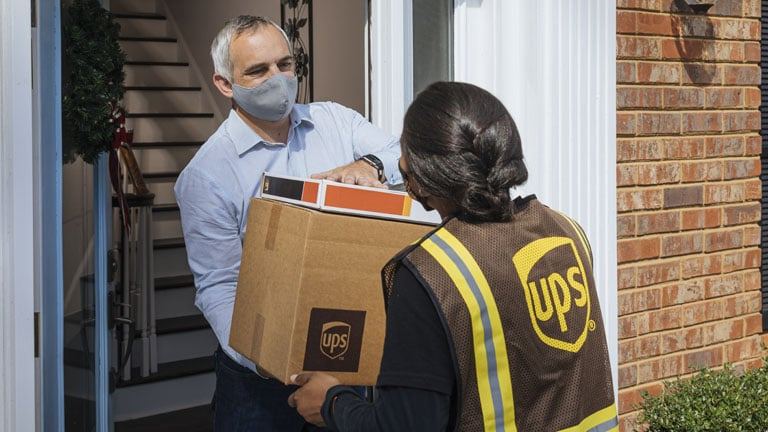 Customer handing packages to UPS driver