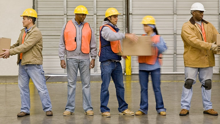 Four diverse workers wearing yellow hard hats and lifting boxes