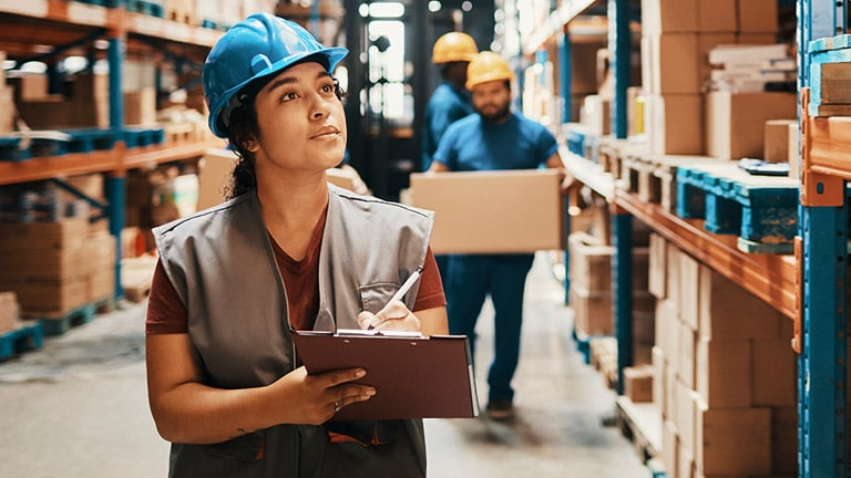 Woman wearing a blue hard hat in a warehouse