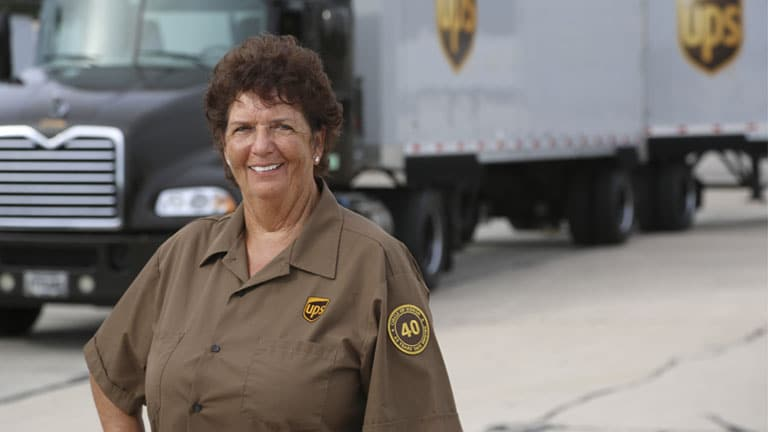 A female UPS package driver standing in front of a truck smiling.