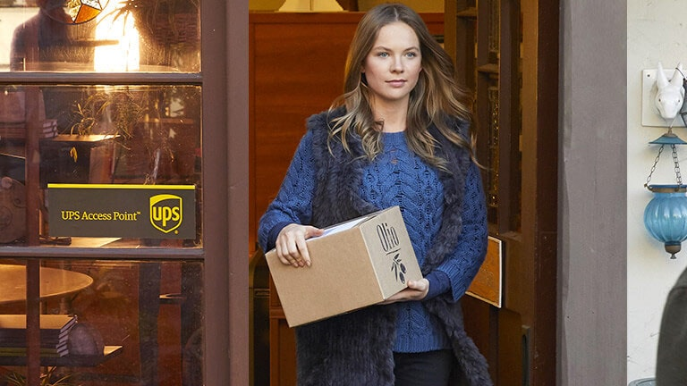 Woman leaving UPS Access Point with parcel
