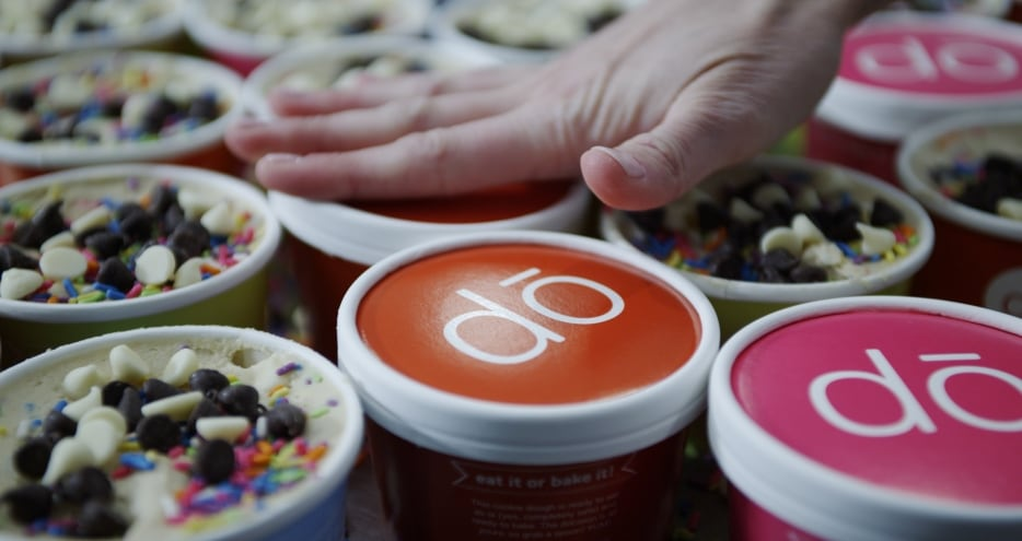Close up photograph of tubs of edible cookie dough covered with chocolate chips and sprinkles