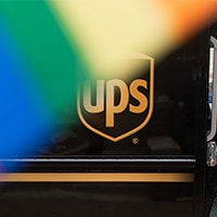 rainbow flag waving with UPS truck in background