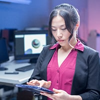 Asian woman in a pink dress shirt touches screen of a notebook computer in an office