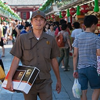 UPS delivery man wheels a dolly with packages through a crowded city square.