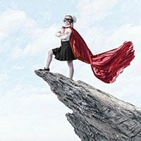 Young girl standing on cliff in superhero cape