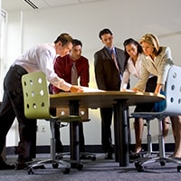 A group of people stand around a conference table looking at paper on the table.