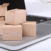 Tiny cardboard shipping boxes sitting on a laptop keyboard
