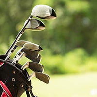 A golf bag filled with golf clubs sits on a lush green golf course.