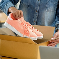 Pink tennis shoes being put in a box