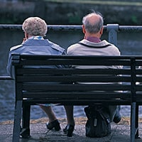 Four old people sitting on a bench.