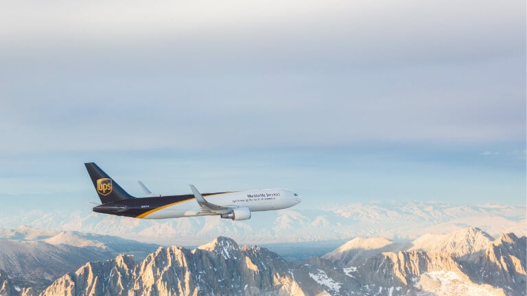 UPS Worldwide Services airplane flying over rugged terrain