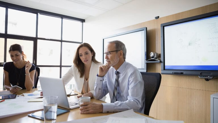 Man and woman looking at a laptop screen in a business meeting