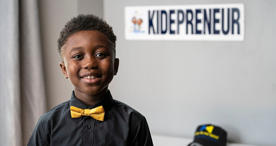 "Elementary school entrpreneur Treandos, founder of T&N Bowties and Apparel, sits in front of a sign reading ""Kidepreneur""."