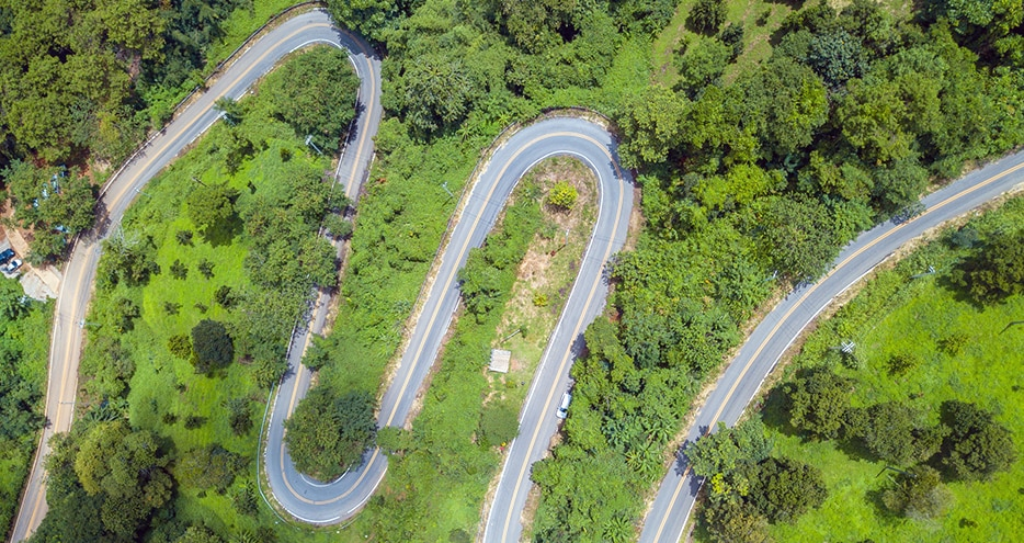 Aerial view of curve road cut through the green forest in the highland mountains in Chiang Rai province, Thailand.