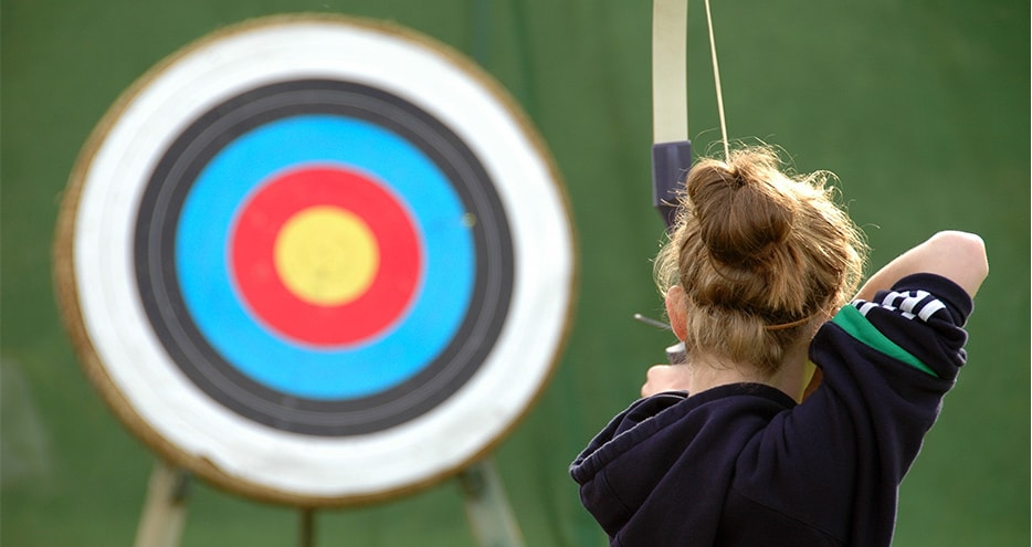 Girl aiming at target with bow and arrow