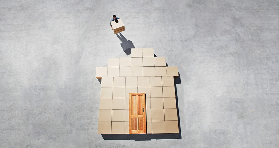 cardboard boxes stacked in the shape of a house