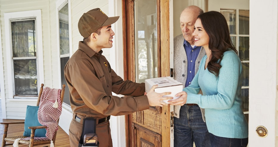UPS driver delivers small box to young woman in a blue shirt and old man at. Does UPS® deliver on Christmas?