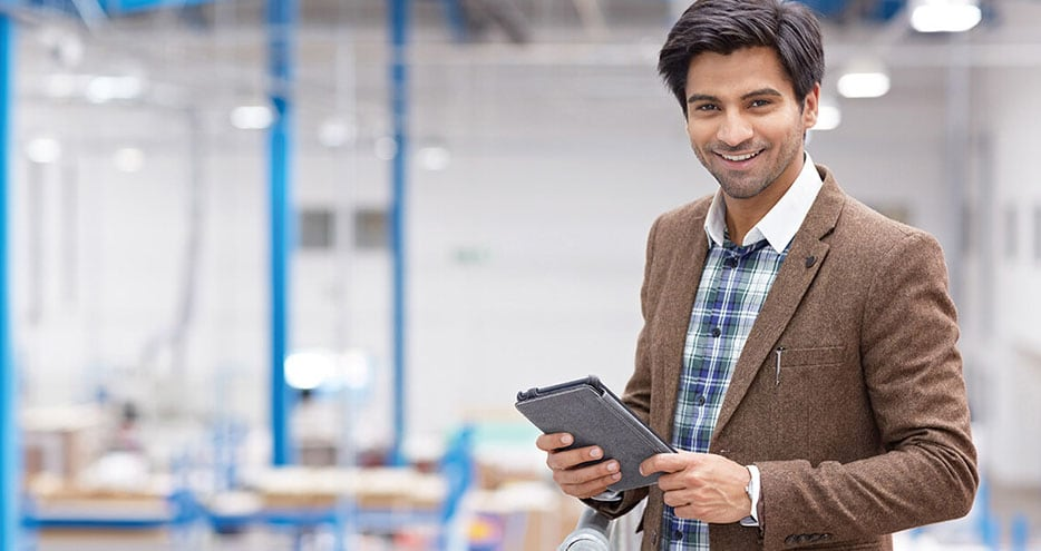 A young businessman carries a mobile device through a warehouse environment.
