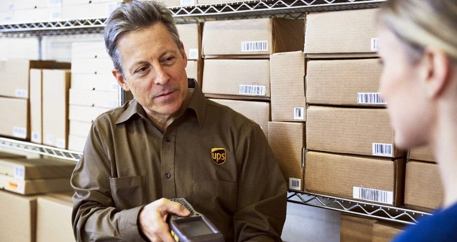 A UPS driver scans a package in a warehouse