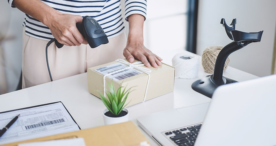 Businesswoman scanning package bar code in office