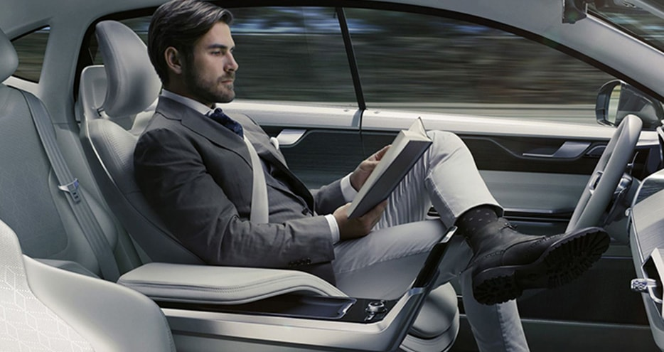 A man sits in the drivers seat, reading a book, as a self-driving car takes him to his destination.