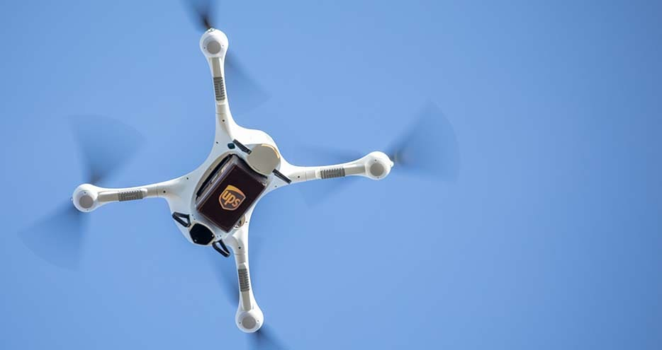 Medical drone flies in the air carrying a UPS package