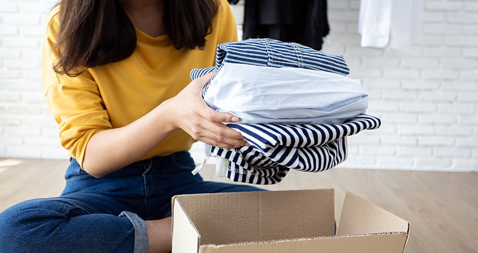 Smiling woman packing clothes in a box.