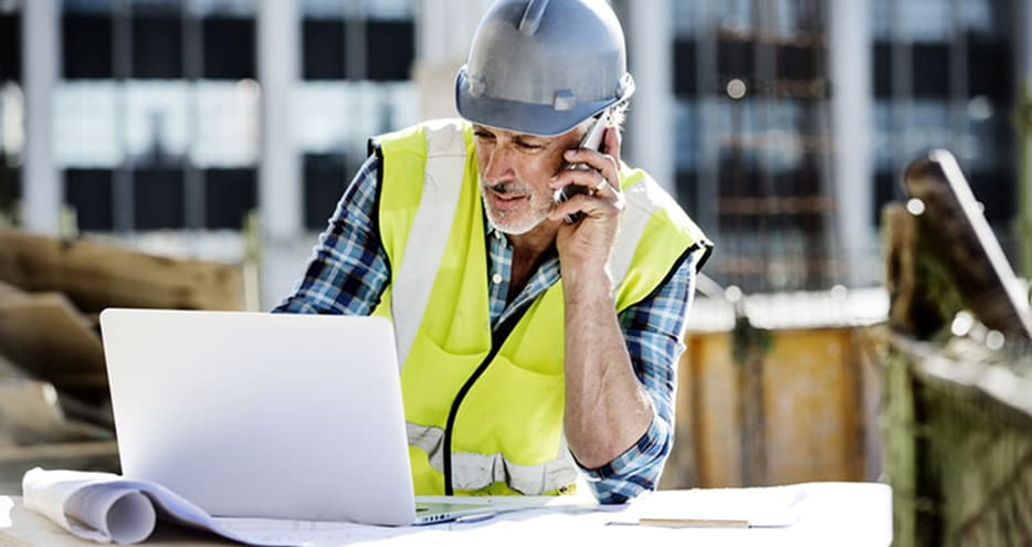 Architect on building site using laptop and phone