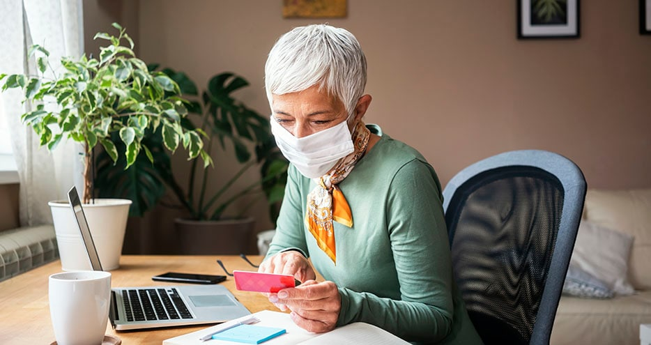 Woman wearing mask using credit card and laptop