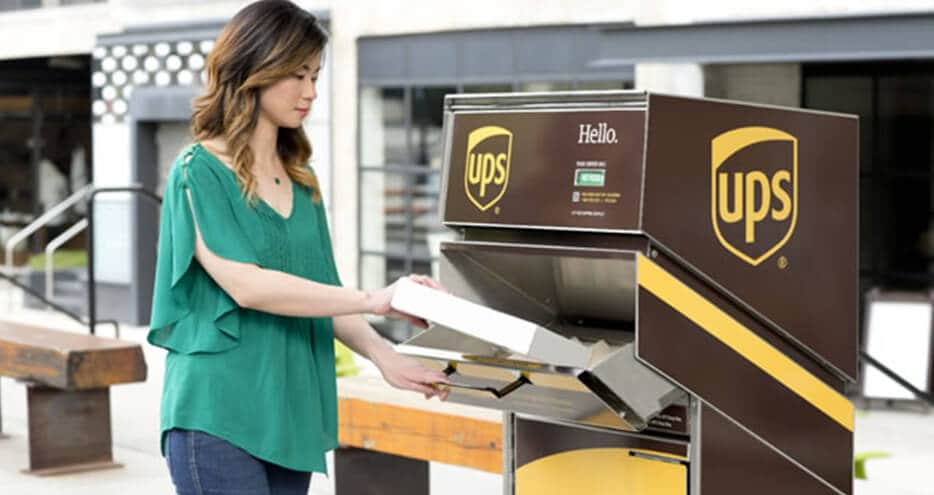 Photo of a woman depositing a box into a UPS drop-off receptacle