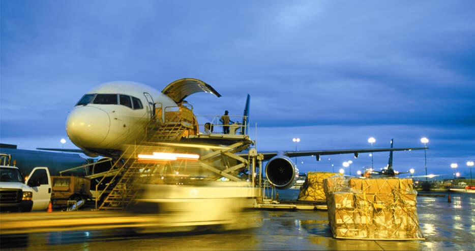 An airplane is loaded with freight as it sits on the tarmac at an airport.