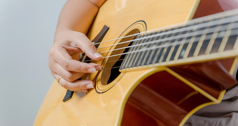 Close-up of a woman's hand playing a guitar.
