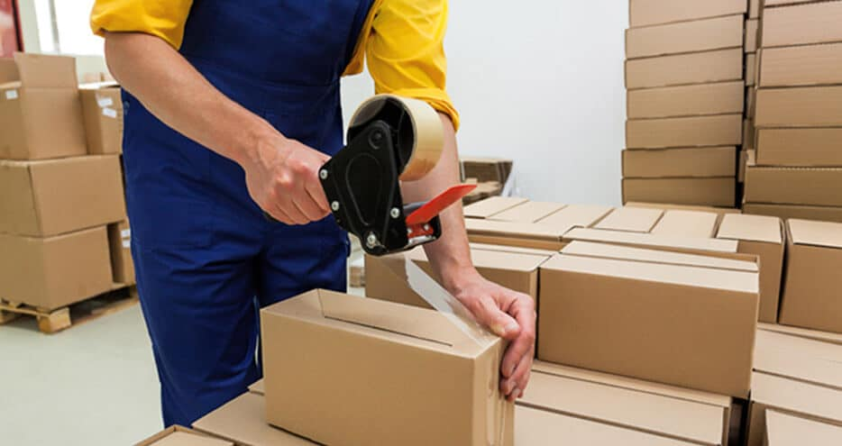 Shipping manager tapes up corrugated boxes