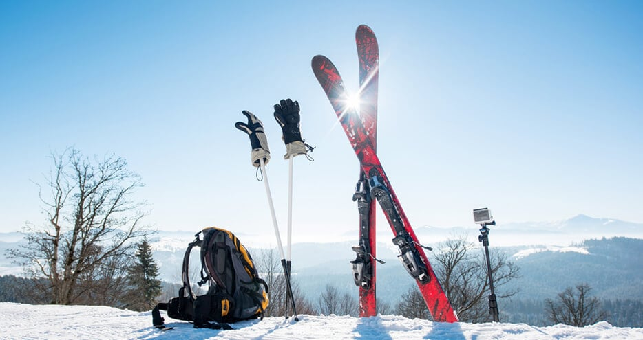 A pair of skis and other gear are waiting to be used on a mountain top.