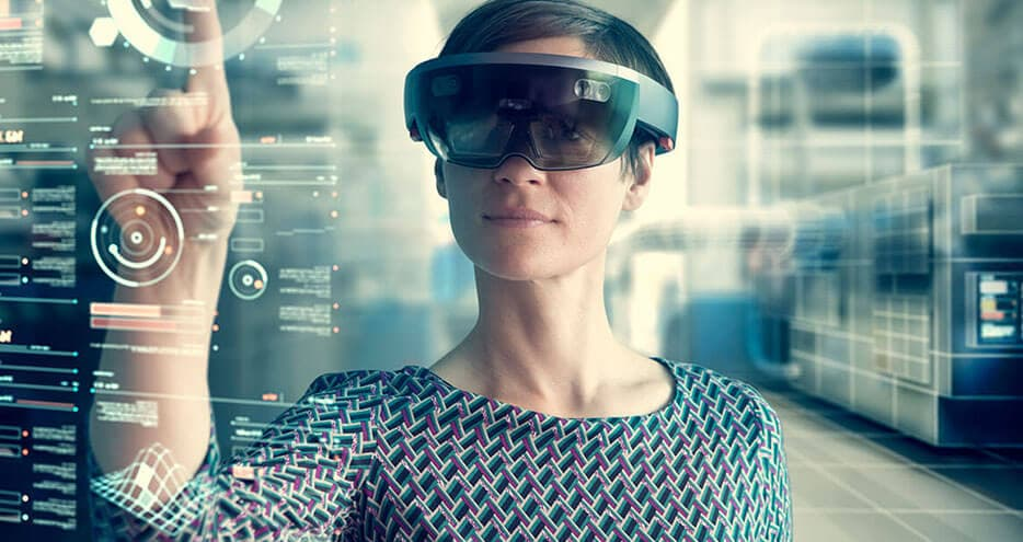 A woman wearing virtual reality goggles stands in front of a glass wall. The diagrams she sees through the glasses are superimposed on the glass in front of her.