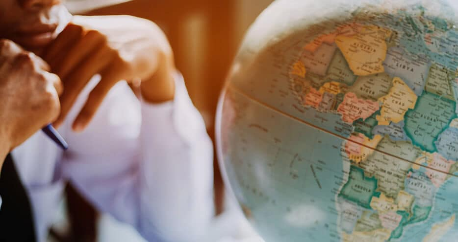 a businessman at a desk contemplates a globe of the earth